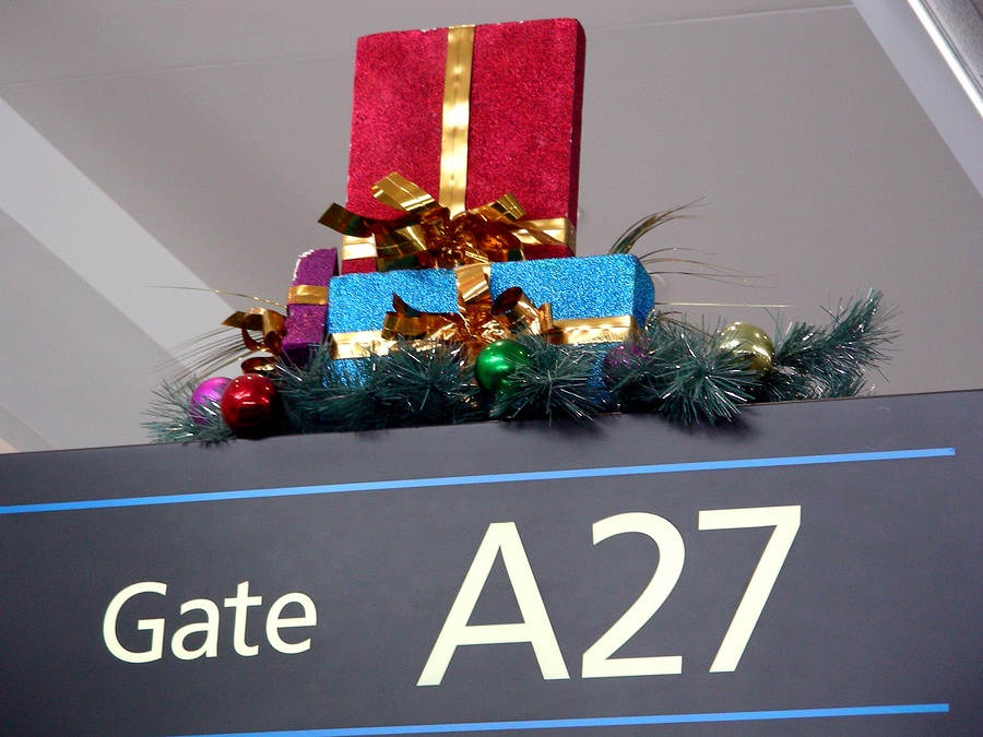 photograph of an airport gate sign, with the gate number A27 featured, and several beautifully wrapped Christmas presents and holiday decorations on the top of the sign
