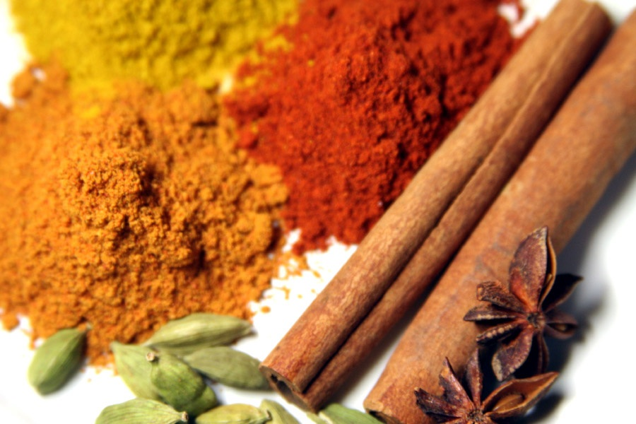 Photo of an assortment of spices, including cinnamon sticks, ground paprika, and ground turmeric